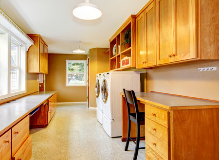 dryer  estate: Spacious laundry room at the horse ranch. Furnished with storage combination and desk with black chair.