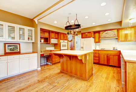 hardwood floor: Country American farm house kitchen interior. Large room with hardwood floor, kitchen island and breakfast area. Northwest, USA
