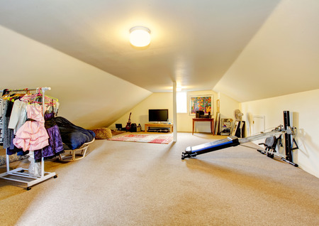 Large long attic game room with tv, musical instruments, sport equipment and Hanger rack with girls clothes . Northwest, USA