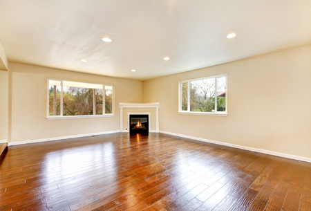 polished: Empty spacious living room with polished hardwood floor and corner fireplace. Northwest, USA