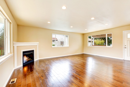 polished: Empty spacious living room in soft beige color with polished hardwood floor and corner fireplace. Northwest, USA
