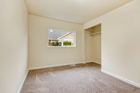 house windows: Small empty room in warm creamy tones with closet, window and carpet floor. Northwest, USA Stock Photo