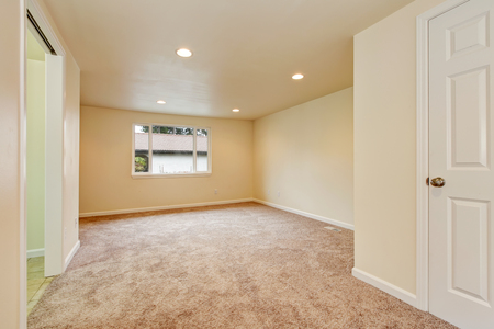 northwest: Empty room interior in creamy colors with carpet floor and one window. Northwest, USA