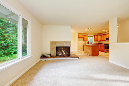 stone fireplace: Nice airy family room with carpet floor and built in  fireplace with stone trim. Kitchen room in the background. Northwest, USA Stock Photo