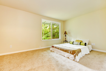 Empty bright bedroom with small bed and lamp, carpet floor and a window. Northwest, USA Stock Photo