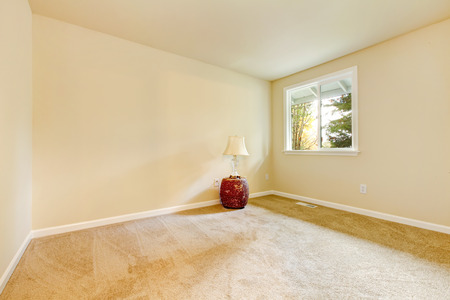 remodeled: Bright beige empty room interior design with one window, carpet floor  and red wicker basket  with lamp on it. Northwest, USA
