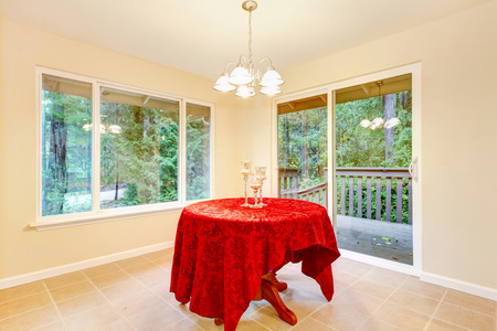 floor cloth: Tile floor dining room interior with elegant red table cloth. The room has exit to back deck. Northwest, USA Stock Photo