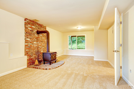 fireplace living room: View of antique fireplace with brick wall in empty living room. Northwest, USA