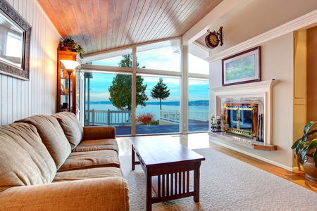 beach view: Awesome living room interior with sloped wooden ceiling, floor to ceiling windows, and amazing view of Redondo beach in Washington. Northwest, USA