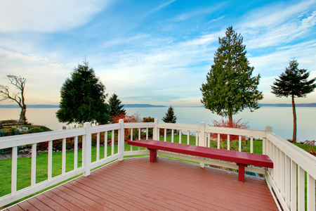 two story: Awesome water view from the wooden deck with red bench of luxury two story house. Northwest, USA