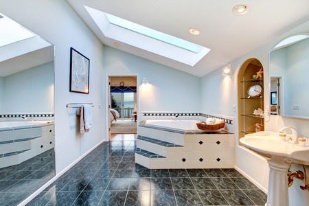 master bath: Master bathroom with blue marble tile floor, corner bath tub with stairs and tile trim, vintage washbasin stand, floor to ceiling mirror and built in shelves with some decor. Northwest , USA