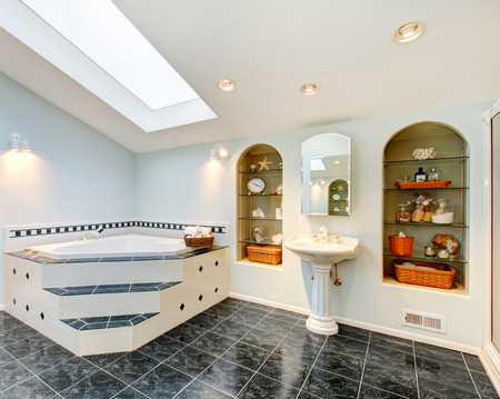 master bath: Master bathroom with blue marble tile floor, corner bath tub with stairs and tile trim, vintage washbasin stand and built in shelves with some decor. Northwest , USA