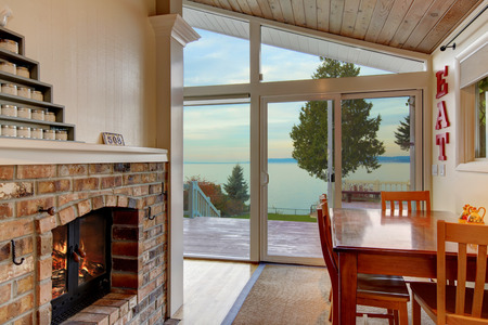 Small dining area with brick fireplace  and water view. Northwest, USA