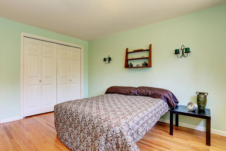 Mint bedroom with hardwood floor and candles on the wall. Northwest, USA