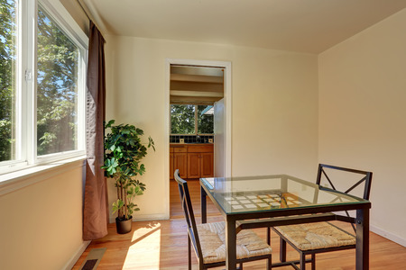 Dining wicker chairs with glass table by the window. Northwest, USA