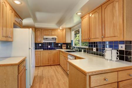 Kitchen room interior with light brown cabinets, white appliances and blue tile back splash trim. Northwest, USA