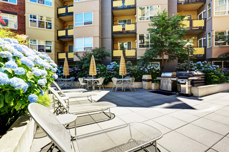 areas: A modern loft courtyard with tables and chairs, barbecue area. New apartment house. Northwest, USA