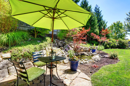 table and chairs: Backyard garden with beautiful landscape. Patio area with umbrella, table and chairs. Northwest, USA Stock Photo