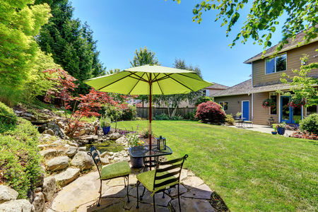 northwest: Backyard garden with beautiful landscape. Patio area with umbrella, table and chairs. Northwest, USA Stock Photo