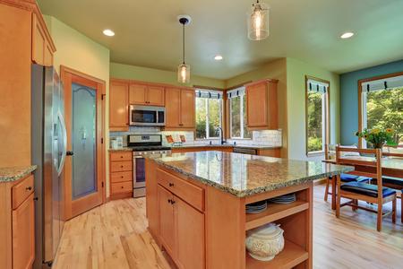 renovated: Light brown kitchen storage combination, kitchen island with granite top and hardwood floor in spacious kitchen room. Northwest, USA