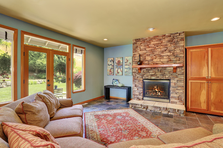 Cozy living room with blue walls, tile floor and stone tile fireplace. Northwest, USA 版權商用圖片
