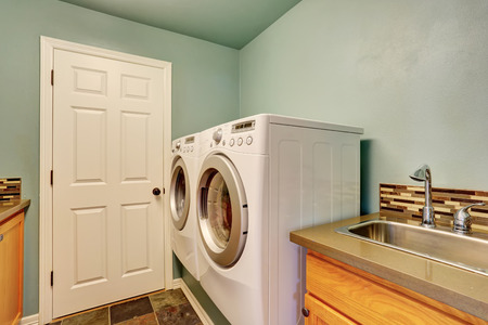 laundry room: Mint laundry room with white appliances and sink. Northwest, USA Stock Photo