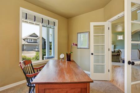 silla de madera: interior de la oficina a casa con escritorio de madera y una ventana. Hay una olla de reloj y la orquídea en la tabla. Noroeste, EE.UU.