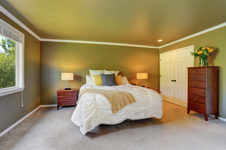 furnished: Gray bedroom interior with chest of drawers and fresh flowers. Big bed with white bedding and yellow pillows. Northwest, USA