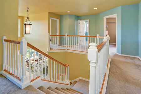 yellow walls: Hallway interior with blue and yellow walls. Staircase with white railings and beige carpet floor. Northwest, USA Stock Photo