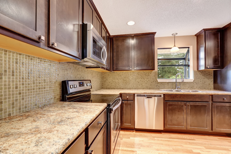 kitchen cabinets: Kitchen interior with brown cabinets and granite tops. Northwest, USA