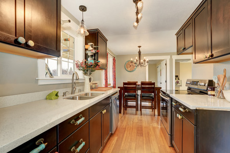 Narrow kitchen interior with deep brown cabinets and granite counter tops. Northwest, USA Stock Photo