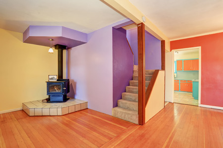 indoor inside: Empty entrance room with staircase  and hardwood floor. Contrast red and violet walls. Vintage fireplace in the corner. Northwest, USA