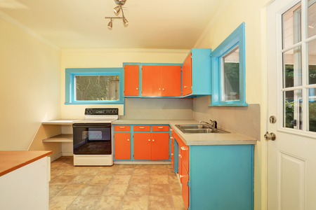 northwest: Old fashioned kitchen interior with orange and blue cabinets. Northwest, USA