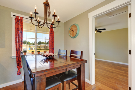 Cozy dining room with large oak table , chandelier and red curtains on the window. Northwest, USA