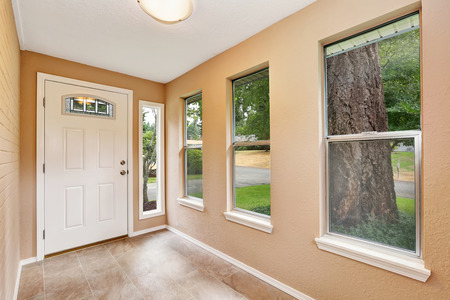 entryway: Empty entryway with tile floor, beige walls and white front Northwest, USA.