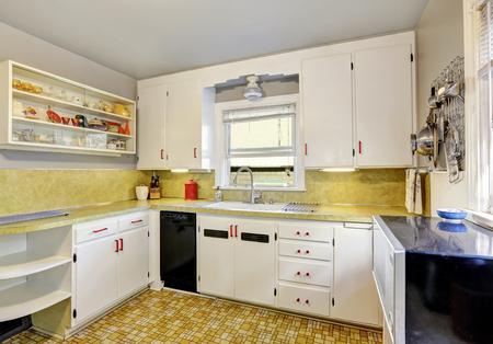 cocina vieja: cocina pasada de moda con armarios blancos, armario empotrado y suelo de linóleo. Noroeste, EE.UU.