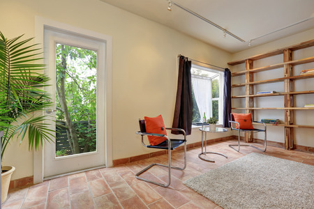 tile flooring: Cozy sitting room with modern chairs, tile flooring and book shelves in apartment house. Northwest, USA Stock Photo