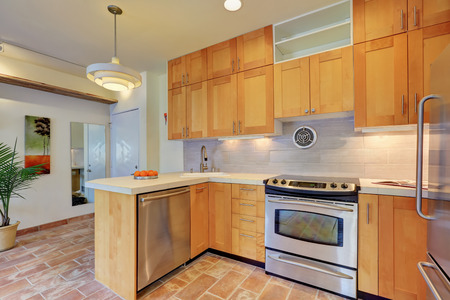 splash back: Light brown kitchen interior with steel appliances and tile back splash trim in apartment house. Northwest, USA