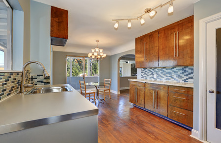 splash back: Kitchen with dining room interior. Dining table with glass top and two maple chairs. Kitchen has steel stove and mosaic back splash trim. Northwest, USA Stock Photo