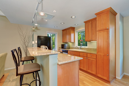 cabinets: Modern kitchen interior with bar and stools. Maple kitchen cabinets and granite counter tops. Northwest, USA