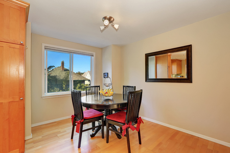 wood flooring: Interior design of dining room. Black table and chair set, vintage mirror on the wall and wood flooring. Northwest, USA
