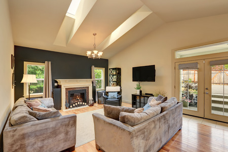 vaulted ceiling: Classic American family room with fireplace and sofas. Has vaulted ceiling with skylight . Northwest, USA