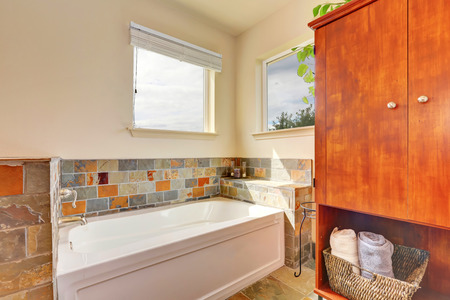 bathtub old: View of bathtub with natural stone tile trim and old wooden cabinet in the bathroom. Northwest, USA