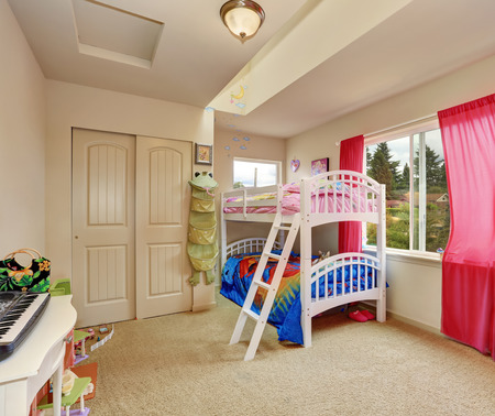 bunk bed: Nice beige kids bedroom. bunk bed with cheerful bedding and red curtains. Northwest, USA