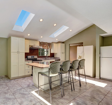 skylights: Bright sunny kitchen with vaulted ceiling and skylights. Old fashioned storage combination, white fridge, kitchen island  with stools and tile floor. Northwest, USA