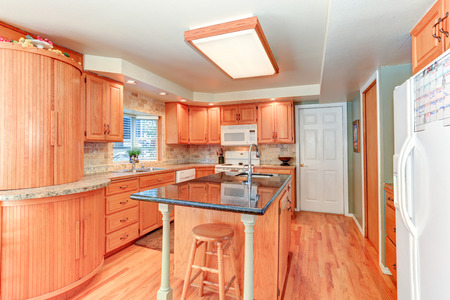 cabinetry: Bright kitchen interior with oak wood cabinetry, kitchen island, tile wall trim. Northwest, USA