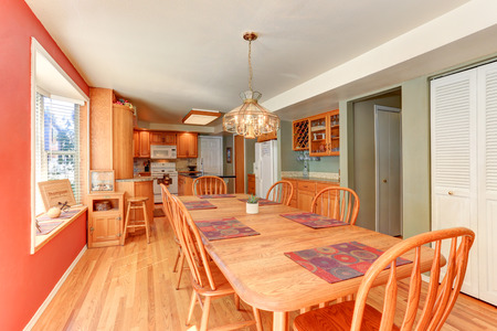 Red dining room interior with large wooden table and chairs. Connected with kitchen room. Northwest, USA