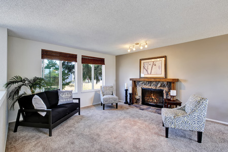 Cozy family room with vintage armchairs and stone trim fireplace. Black sofa and beige carpet. Northwest, USA 版權商用圖片 - 61274887