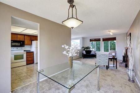 Lgante salle à manger lumineuse avec table en verre et un joli décor. Sortie sur le balcon. Northwest, États-Unis Banque d'images - 61274889