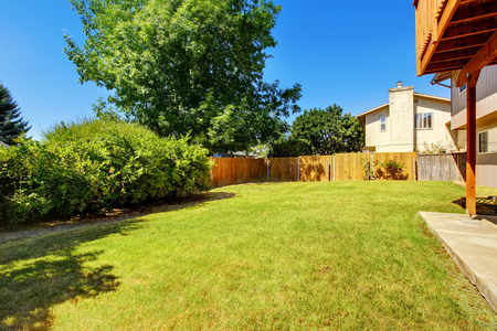 northwest: Fenced backyard with green lawn and bushes. Northwest, USA